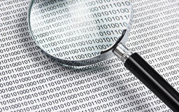 Magnifying glass on a binary code Royalty Free Stock Photography