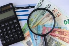 Magnifying glass and black calculator on pile of Euro banknotes Royalty Free Stock Photo