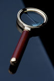 Magnifying glass on black table. Classical magnifying glass lying on black mirror surface stock photos