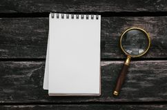 Magnifying glass and blank page note pad. Magnifying glass and blank page notepad on old aged wooden table background Royalty Free Stock Photography