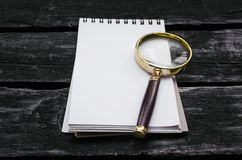 Magnifying glass and blank page note pad. Magnifying glass and blank page notepad on old aged wooden table background Royalty Free Stock Images