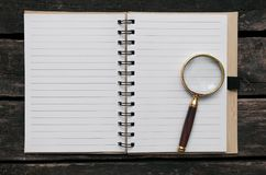 Magnifying glass and blank page note pad. Magnifying glass and blank page notepad on old aged wooden table background Stock Images