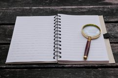 Magnifying glass and blank page note pad. Magnifying glass and blank page notepad on old aged wooden table background Royalty Free Stock Photos