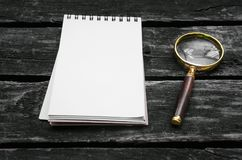 Magnifying glass and blank page note pad. Magnifying glass and blank page notepad on old aged wooden table background Stock Image