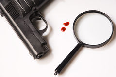 Magnifying glass, blood drops and pistols Royalty Free Stock Photos