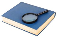 Magnifying glass on a blue book Royalty Free Stock Photos
