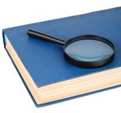 Magnifying glass on a blue book Royalty Free Stock Image