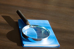 Magnifying glass on blue book Stock Images