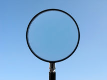 Magnifying Glass on blue sky background royalty free stock photography