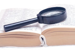 Magnifying glass on a book. Old book and a magnifying glass Royalty Free Stock Images
