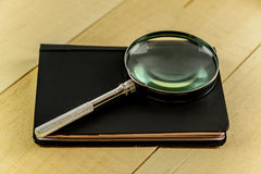 Magnifying Glass and Book on Pine Table Stock Photos