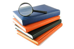 Magnifying glass on books Royalty Free Stock Photo