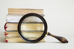 Magnifying glass and books royalty free stock images