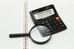 Magnifying glass and calculator on the notebook Royalty Free Stock Image