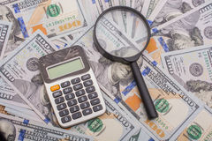 Magnifying glass  and calculator over the US dollar banknotes Royalty Free Stock Photo