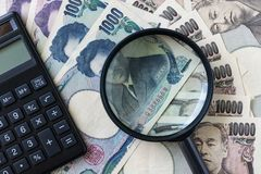 Magnifying glass and calculator on pile of japanese yen banknote Royalty Free Stock Photography