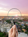Magnifying glass and cityscape in focus Stock Photo