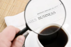 Magnifying glass with coffee cup and newspaper Stock Photography