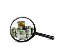 Magnifying glass with coin closeup on white background. For business profit and financial concept royalty free stock photo