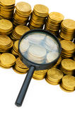Magnifying glass and coins Royalty Free Stock Photography