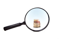 Magnifying glass with coins Royalty Free Stock Photos