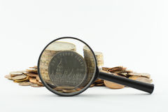 Magnifying glass and coins Stock Photos