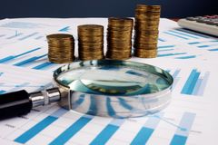 Magnifying glass and coins. Investment and wealth audit. Concept royalty free stock photography