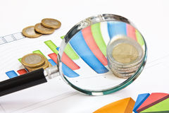 Magnifying glass and coinss Royalty Free Stock Photo