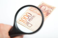 Magnifying Glass on the Colombian Pesos.  Royalty Free Stock Images