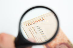 Magnifying Glass on the Colombian Pesos. Isolated Royalty Free Stock Photos