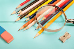 Magnifying glass with colorful pencil Stock Photos