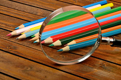 Magnifying glass with colorful pencil. On wooden table Royalty Free Stock Images