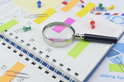 Magnifying glass with colorful post It notes and pin on diary pa Royalty Free Stock Photography