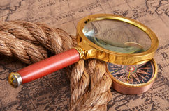 Magnifying glass and compass on the ancient map Royalty Free Stock Images