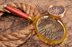 Magnifying glass and compass on the ancient map Stock Photo