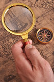 Magnifying glass and compass on the ancient map Stock Image