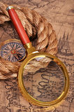 Magnifying glass and compass on the ancient map Royalty Free Stock Image