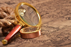 Magnifying glass and compass on the ancient map Royalty Free Stock Photo