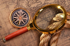 Magnifying glass and compass on the ancient map Royalty Free Stock Photos