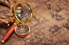 Magnifying glass and compass on the ancient map Stock Images