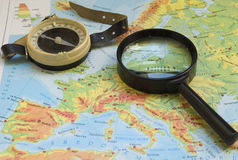 Magnifying glass and a compass on a map Stock Photos