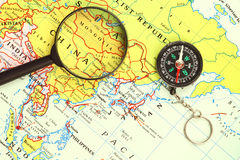 Magnifying glass , a compass and a map Royalty Free Stock Images