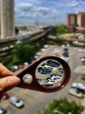 Through magnifying glass on Coney Island. A view through a magnifying glass on a parking lot with Coney Island amusement park and MTA New York subway West 8th stock photo
