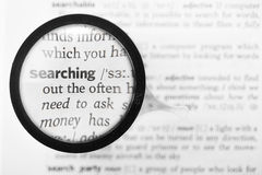 Magnifying glass and dictionary definition of the word searching Stock Image