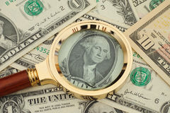 Magnifying glass and dollar bills Stock Photos