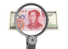 Magnifying glass, dollar and Chinese yuan Royalty Free Stock Images