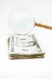 Magnifying glass with dollars Royalty Free Stock Images
