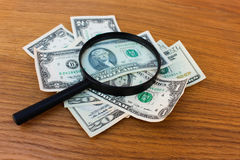 Magnifying glass and dollars Stock Images
