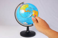 Magnifying Glass on Earth Globe on White Stock Photos