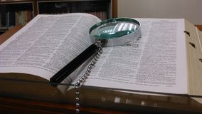 Magnifying glass and encyclopedia Stock Images